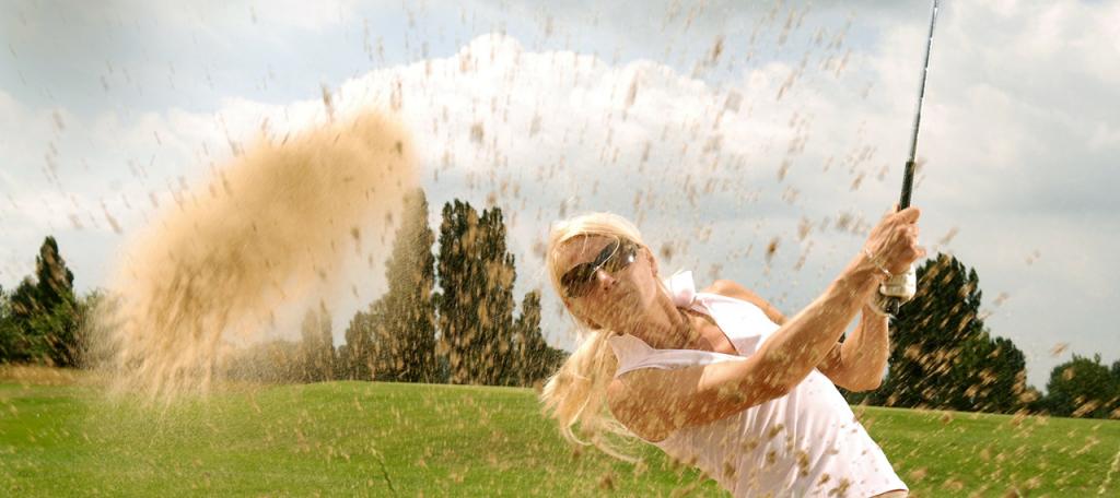 Vrouw slaat golfbal uit de bunker met veel opspattend zand als gevolg Golfreizen Luxe Golfreis Algarve, Beste prijs kwaliteit verhouding, golf travel